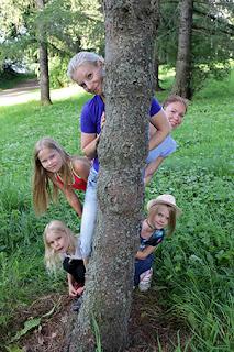 Kirsi Käyhty kurkkaa lasten kanssa puun takaa.