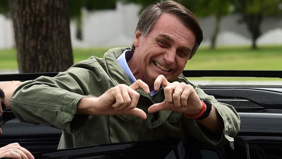 Jair Bolsonaro saluda a su militancia luego de emitir su voto en Rio de Janeiro / AFP
