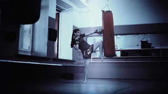 Woman hitting the punching bag, martial arts, heavy bag