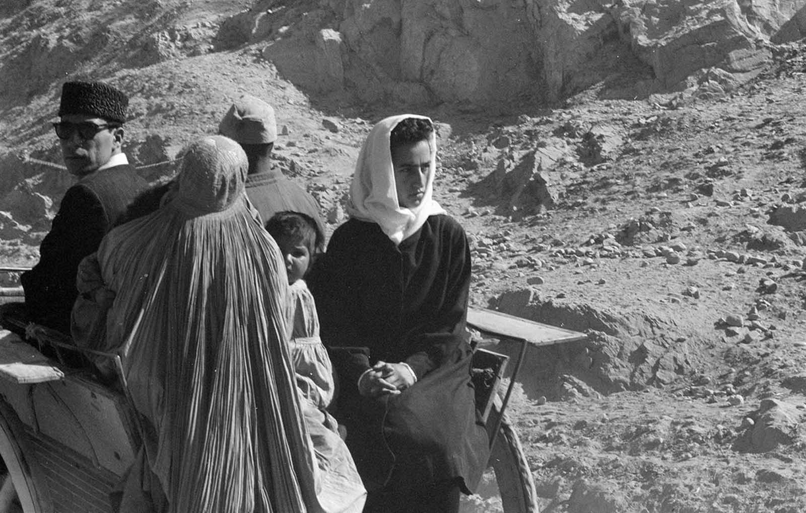 Afghan women, men, and child in traditional dress ride in a cart through an arid, rocky landscape, November, 1959.