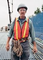 Beton atılan bir inşaatta baret ve gözlük takmış kırmızı yelekli inşaat işçisi