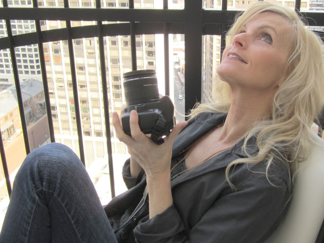 blonde holding camera aimed at sky on waldorf astoria balcony by Hello Lovely Studio