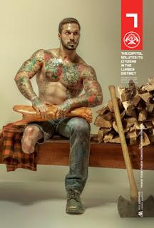 A foto mostra o modelo Alex Minsky, ex-fuzileiro naval que lutou no Afeganistão. Alex está sentado em um banco de madeira, à direita, próximo a ele, uma pilha de achas de lenha e o cabo de um enorme machado encostado na pilha. Alex é um homem de pele bronzeada, rosto oval, cabelos curtos castanhos claros, sobrancelhas levemente arqueadas, nariz reto, lábios médios, bigode e barba por fazer; está desnudo da cintura para cima evidenciando uma tatuagem colorida que envolve os torneados braços, musculoso peito e o bem definido abdômen; ele segura a parte inferior de uma perna mecânica sobre as coxas; perna esquerda com calça jeans surrada e sapato gasto e parte do joelho direito a mostra com a parte da calça cortada acima do joelho. À esquerda, sobre o assento, uma camisa xadrez em ocre, marrom e preto.