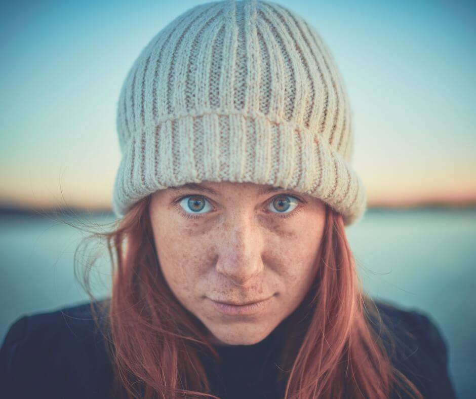 "A woman wearing a wool beanie hat stares straight into the camera, a serious look on her face. She has ginger hair and freckles cover her face. She has green eyes. She is wearing a dark blue top. The horizon is blurred in the background but a dark line separates the sky from the sea. Image for ""Things I've learned about myself since becoming a mother"""