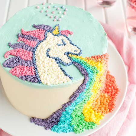 image of a cake featuring a unicorn puking a rainbow