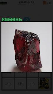 На столе стоит камень красного цвета