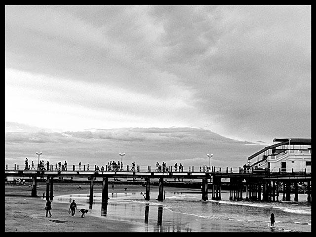 Cielo tormentoso sobre la playa con personas.