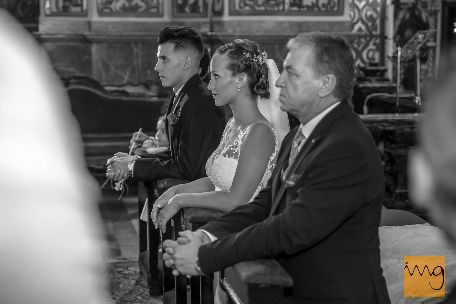 Fotografía de los novios arrodillados frente al altar el día de su boda