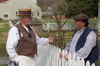 Two men stand on either side of a white picket fence. Man on left wears a long-sleeved white shirt, brown vest, and straw boater hat. Man on right wears a long-sleeved check shirt, blue vest, and a brown cap.