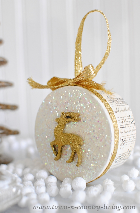 little round boxes decorated with deer and sheet music and lots of glitter