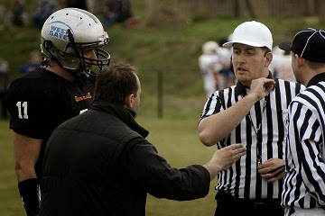 Football coach arguing with referee on the pitch