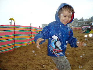 Big Boy playing on the beach in the rain
