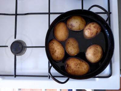 Sieben Kartoffeln in einem schwarzen Emailletopf