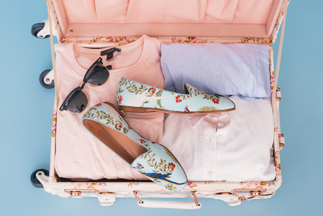 Pink suitcase filled with bright clothes, patterned shoes and sunglasses