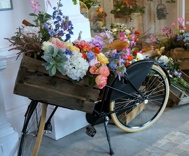 vintage bicycle with basket of flowers inside the florist, liverpool