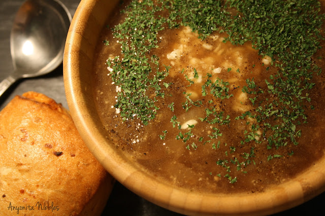 A bowl of French onion soup with a cheese roll.