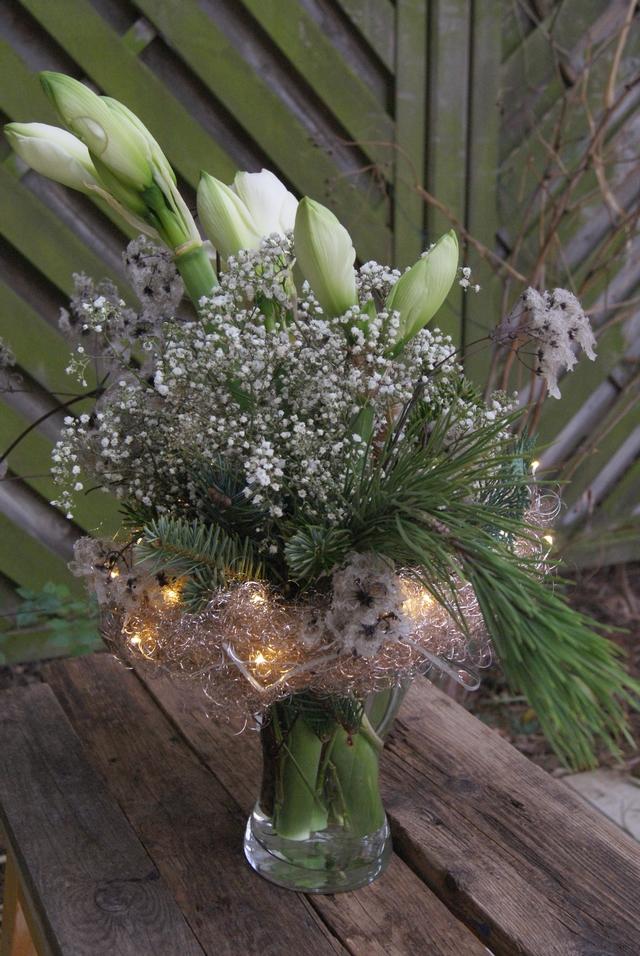 Amaryllisstrauß mit Lichterkette und gewachsten Blüten