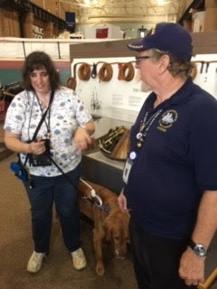Woman with guide dog talks with man in exhibit gallery at Erie Maritime Museum