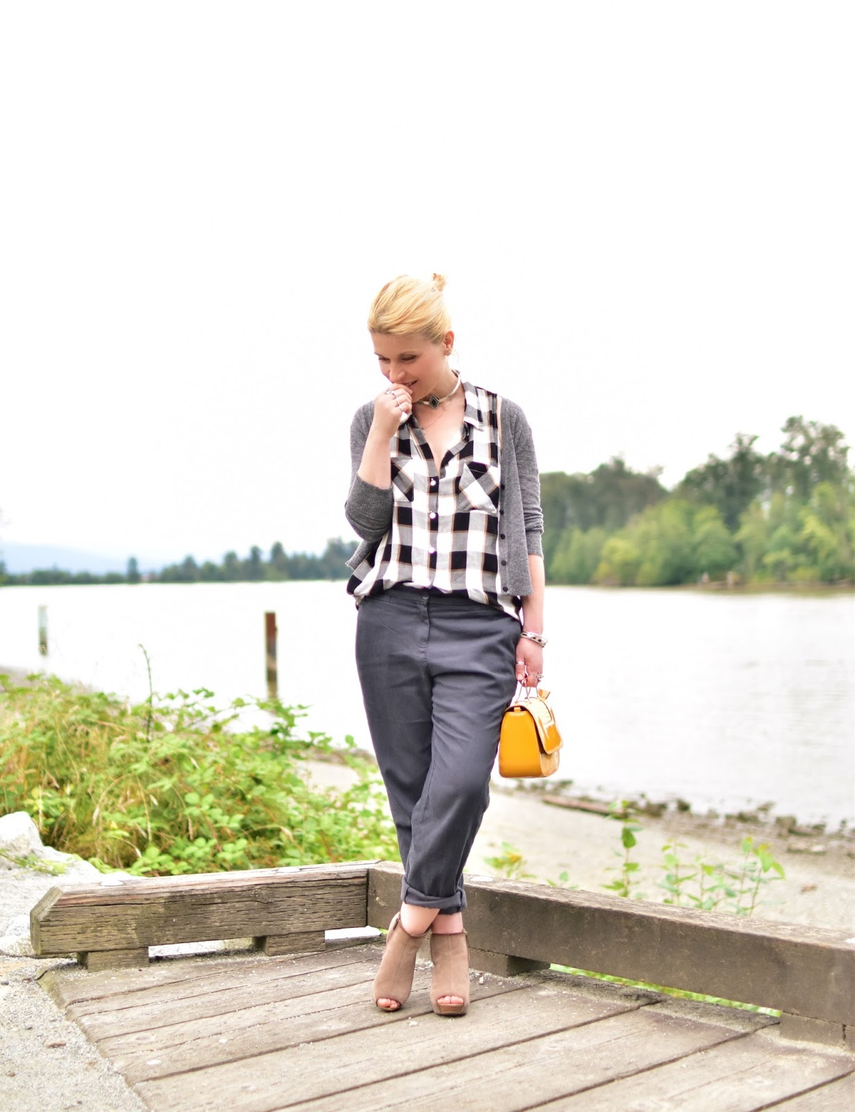 styling a plaid button-front shirt with slouchy boyfriend trousers, cropped cardigan, open-toe wedge booties, and patent yellow bag