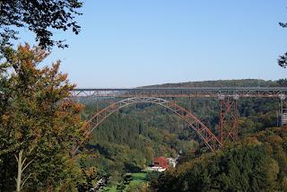 Die Müngstener Brücker spannt sich üher die Wupper, umgeben von herbstlichen Wäldern.