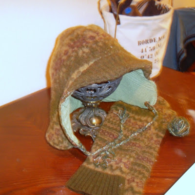 Earflap cap with brim, constructed from repurposed sweaters. Outer layer is of boiled wool, patterned in shades of olive and brown, with the brim a solid olive ribbing. Inner layer is of light green ribbed material. With the hat is a pair of arm-warmers, cut from sleeves of the sweater that forms hat's outer layer. In background: a canvas tote holds thread and pieces of hats for sewing.