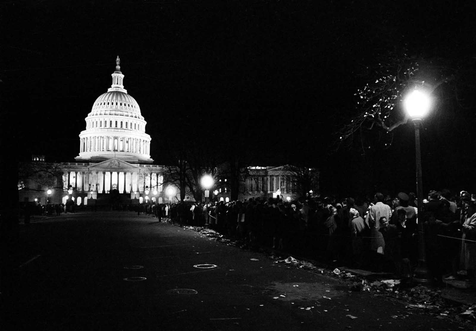 With the illuminated U.S. Capitol in the background, mourners form an endless line which lasted through the night, to pay their respects to the slain President John F. Kennedy, in Washington, District of Columbia, on November 24, 1963.