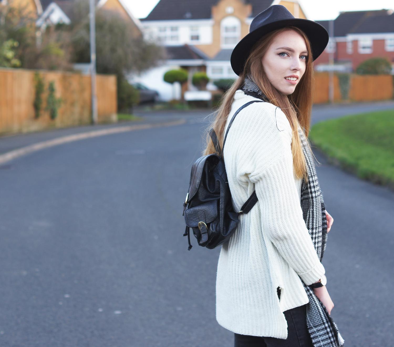black backpack and fedora