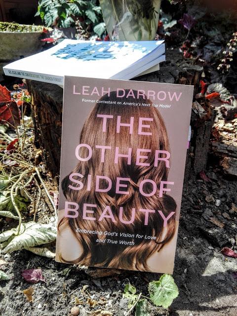 Kaft van het boek van Leah Darrow The Other side of Beauty met een tuin op de achtergrond.