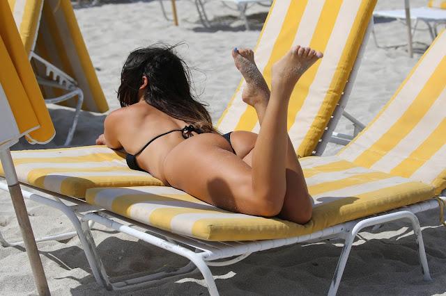 Claudia Romani in an black bikini on the beach in Miami