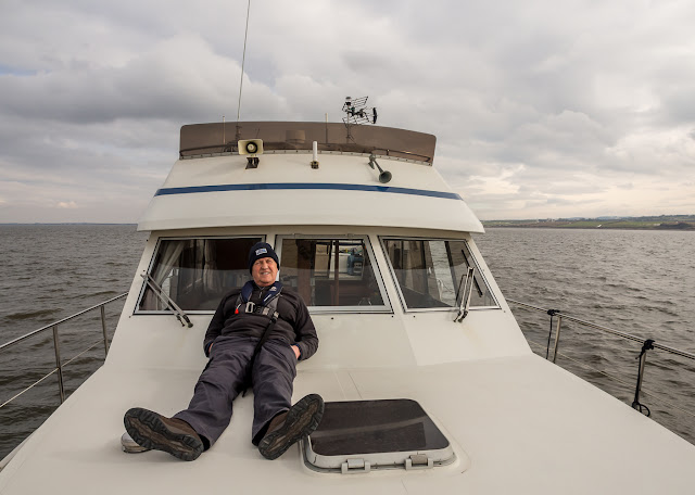 Photo of Phil laying on Ravensdale's foredeck waiting for a bite
