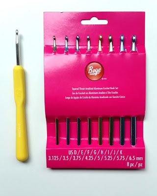 A yellow-handled Boye aluminium hook (G6-4.25mm) and a set of 8 coloured anodised aluminium straight hooks (sizes D-K) in a pink cardboard packet.