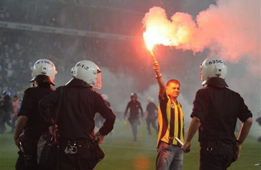 Riot police seen trying to control a fan during clashes with Fenerbahçe supporters