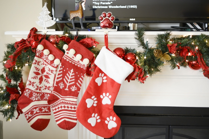 Christmas stockings with garland around mantle