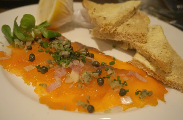 garnished smoked salmon with brown bread and lemon wedge