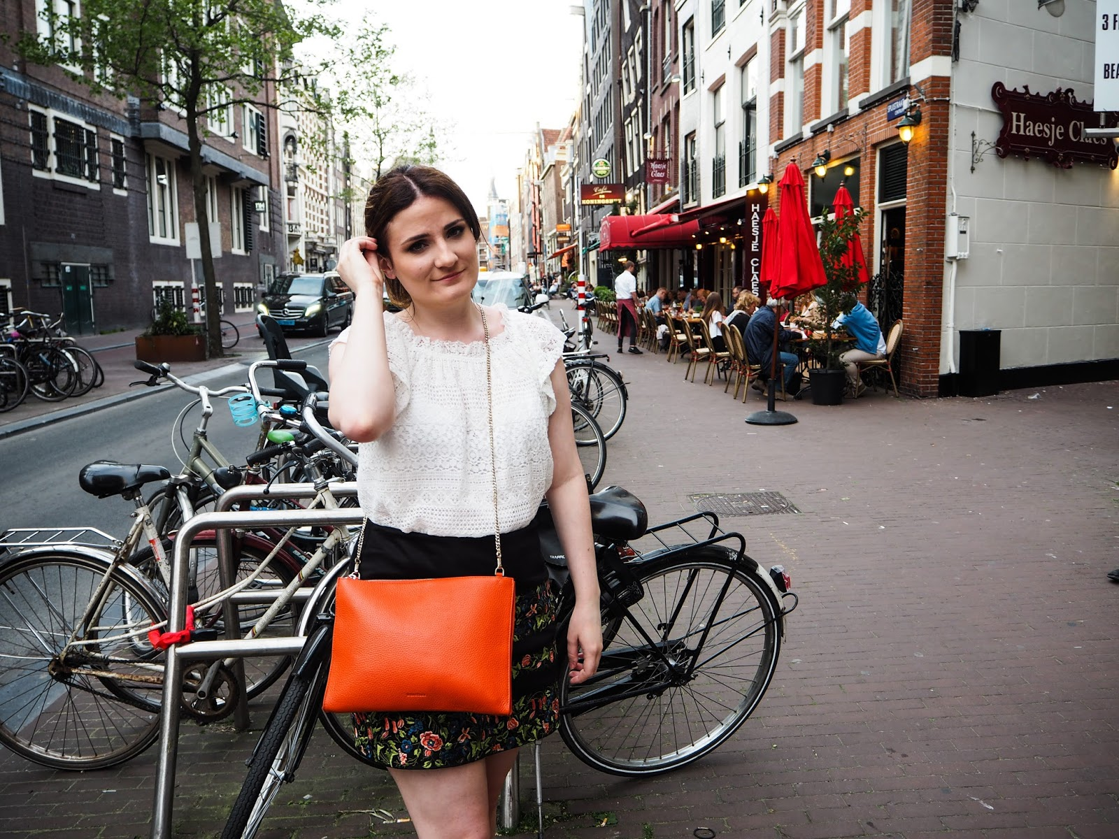 Fashion blogger posing with Orange Whistles Chain Bag
