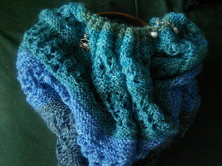 A Garter stitch and lace shawl still live on the needles.  It is knit in gradient stripes from dark blue to teal green.  There are stitch markers visible in the work -- a small silver crab, and small silver shells.