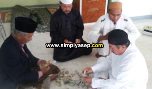 HITUNG : Hasil perolehan kotak kaleng atau kotak amal yang berjalan selama pelaksanaan Sholat Idul Fitri di Masjid Babussalam Duta Bandara sedang dihitung oleh pengurus masjid (15/6). Foto Asep Haryono