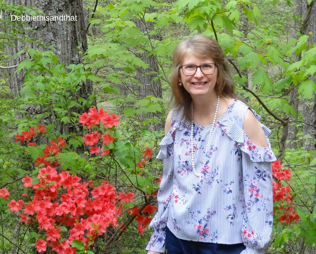 standing next to the azaleas wearing a cold shoulder top