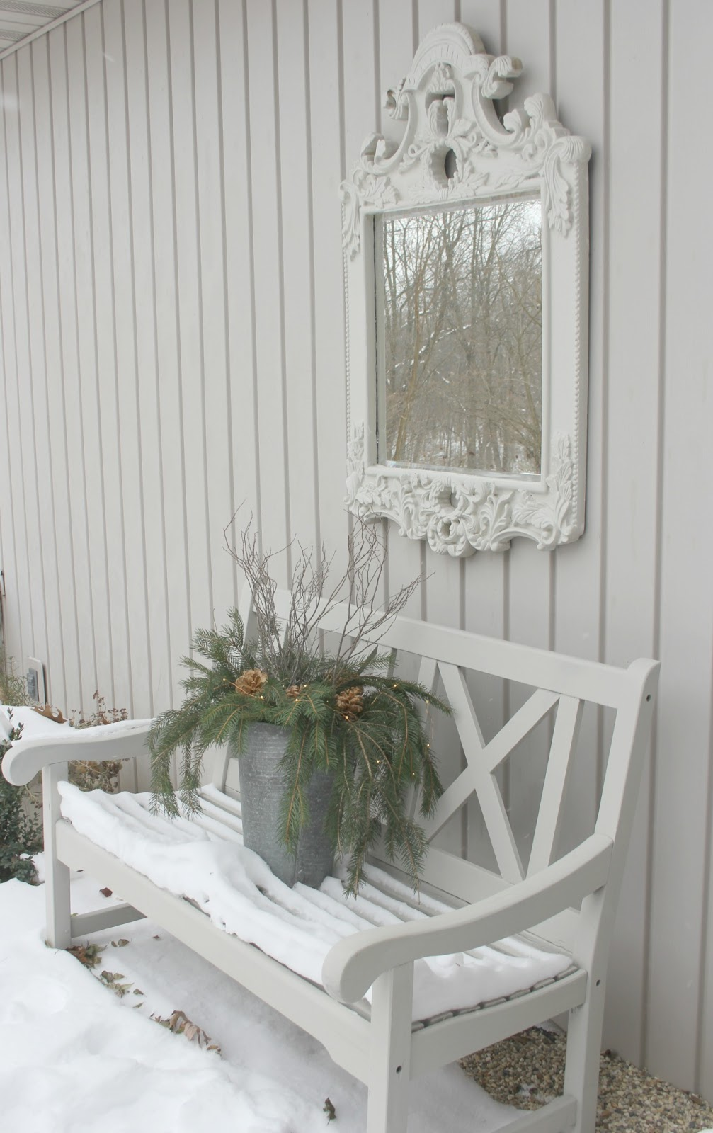 Winter holiday vignette with snow, white bench, and French mirror - Hello Lovely Studio