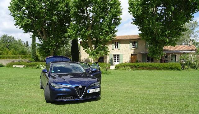 Alfa Romeo Giulia Super auf grünem Rasen mit offenem Kofferraum und Türen