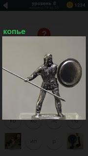 На подставке стоит статуэтка рыцаря воина с копьем и щитом