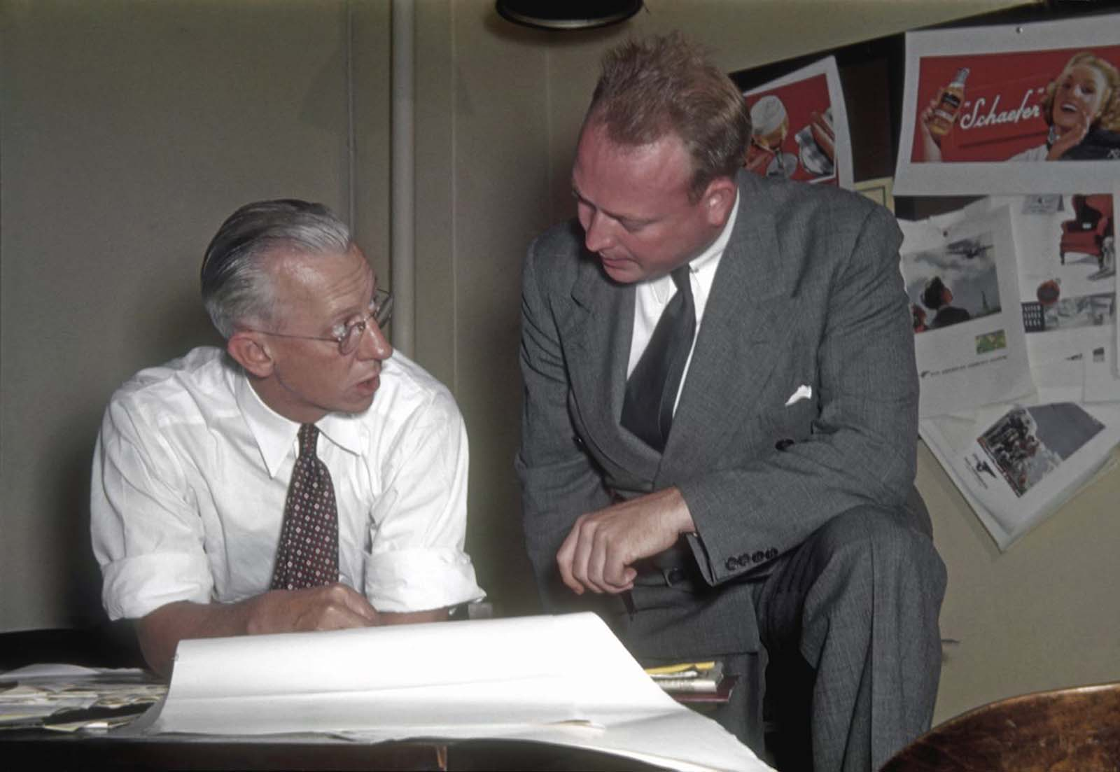 Two ad men discuss a campaign, a pinboard behind them is covered with a range of spreads, including one for Schaefer beer.