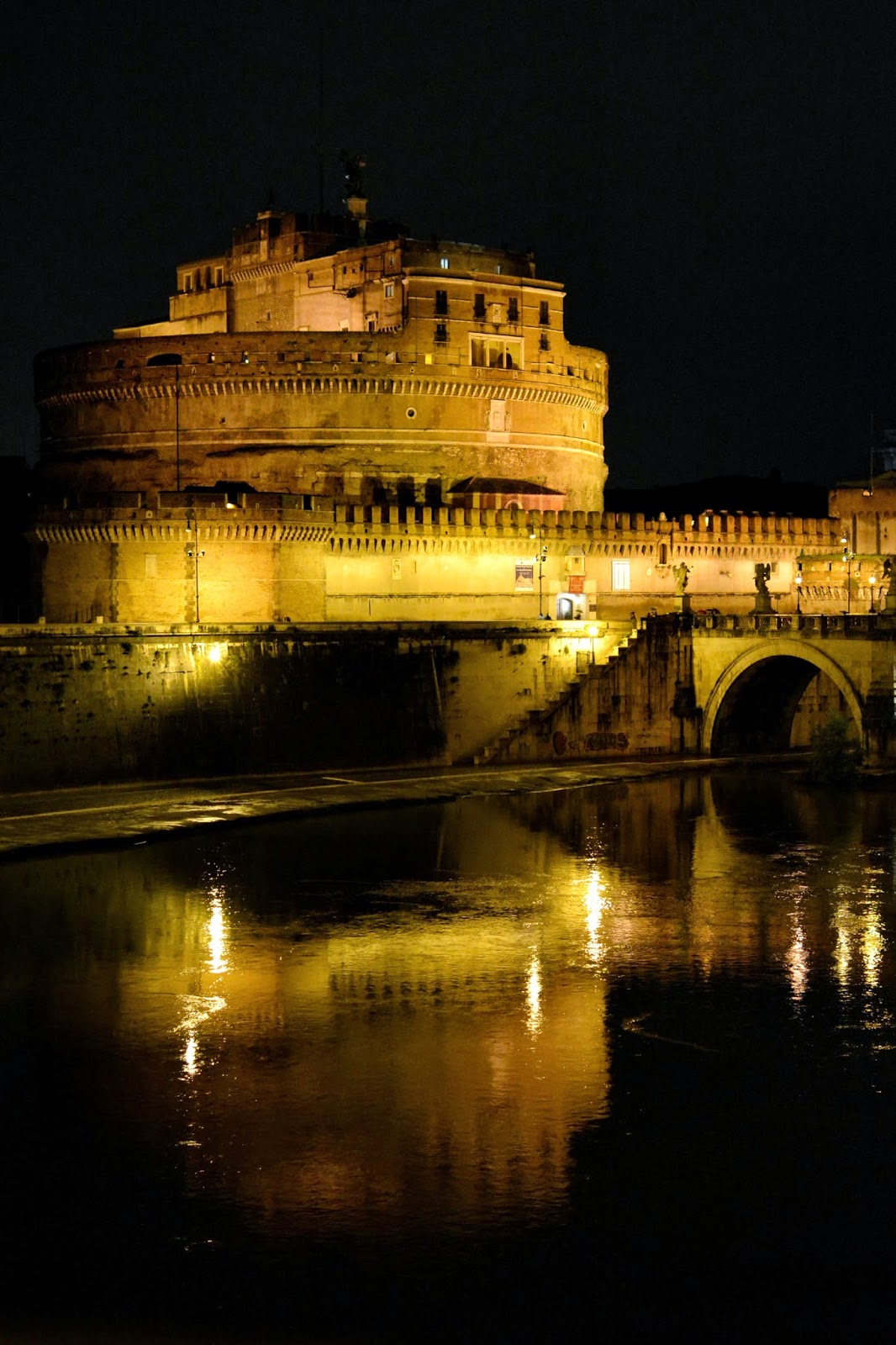 Night time photograph of Castel Sant'Angelo and the River Tiber
