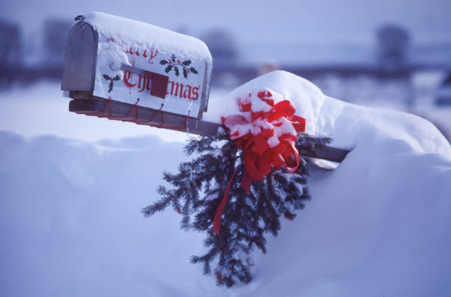 American style mailbox sticking out of the snow with Merry Christmas written on the side