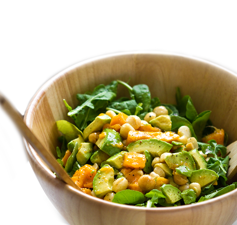 Salad with arugula avocado mango and nuts in large bowl