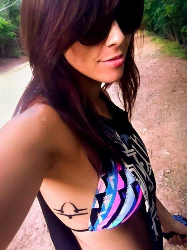 chica morena en un bosque, va en bikini, vemos un tatuaje en las costillas