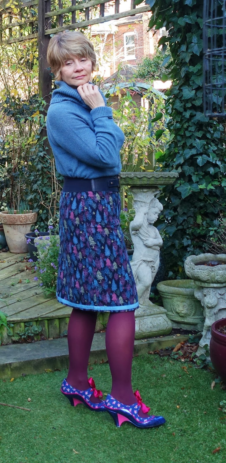 Image showing a 50 plus woman wearing a patterned skirt with a tree print in blue and mauve shades and a toning blue sweater