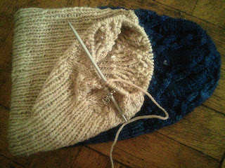 A doubled hat.  The blue hat has stitches picked up from the bottom brim and knit with white yarn, to create a second hat, joined at the bottom brim. The hat is a worsted-weight cabled hat.