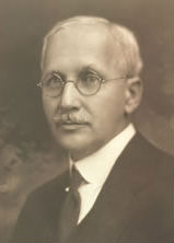 An old photograph of a balding, middle-aged white man with round wire-rim spectacles and a neatly trimed moustache, wearing a suit with a stiff collar.