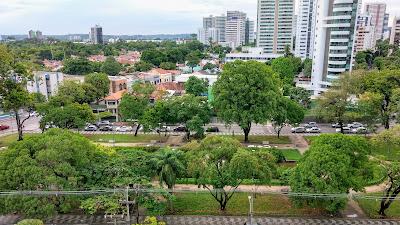 Foto colorida da praça e do bairro Casa Forte. Em primeiro plano, a praça repleta de árvores. Por trás, casarões e edifícios.